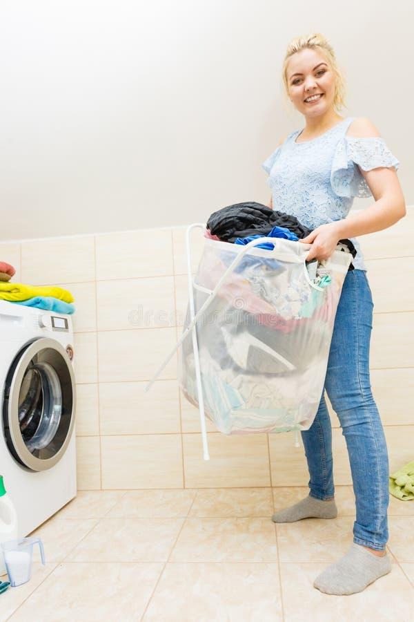 A mulher leva a cesta grande da lavanderia suja da roupa fotos de stock royalty free