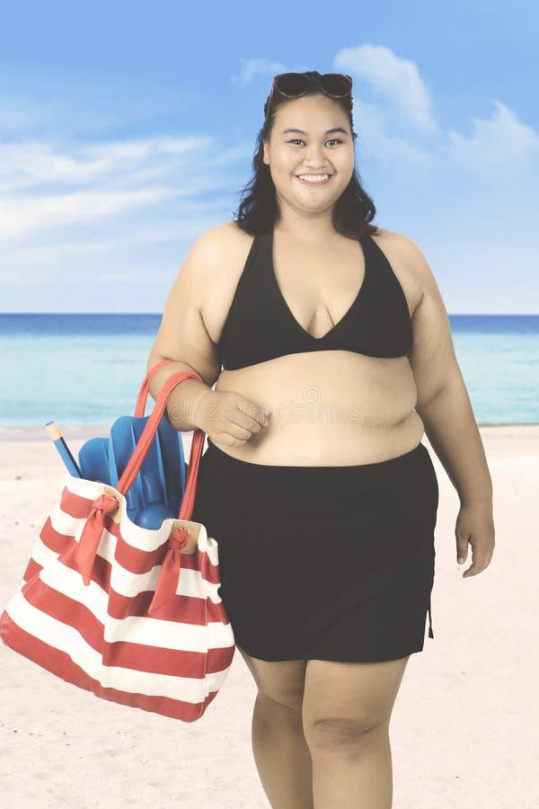 A mulher leva o equipamento do tubo de respiração na praia imagens de stock royalty free