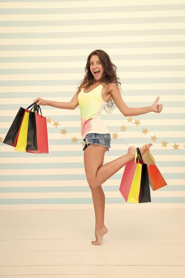 A mulher leva o fundo listrado sacos de compras do grupo Tipo favorito finalmente comprado Vendas da loja das pontas Menina satis foto de stock