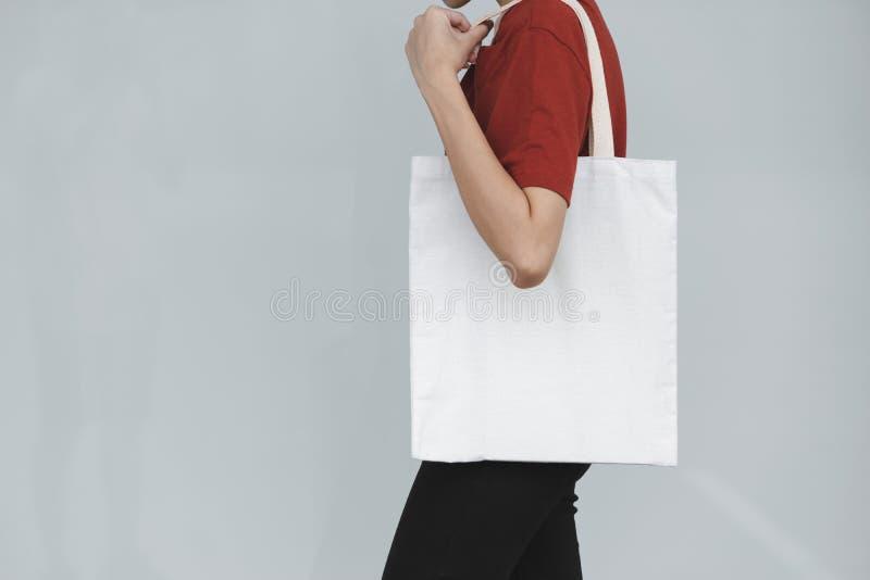 A mulher leva o saco no fundo cinzento no conceito de salvaguarda da terra ou não diz nenhum saco de plástico fotos de stock royalty free