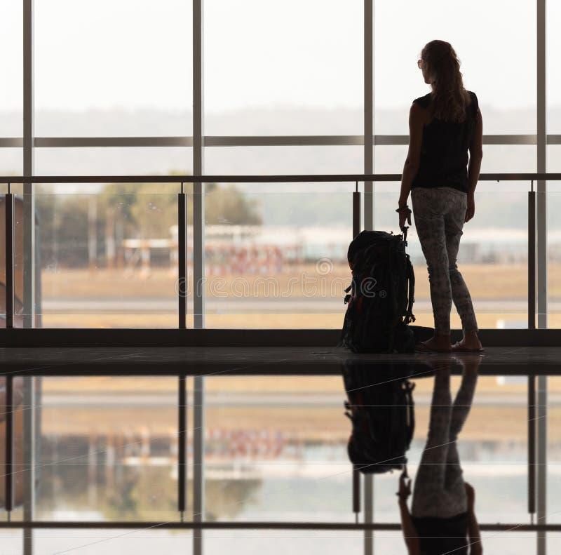 A mulher leva sua bagagem no terminal de aeroporto imagens de stock royalty free