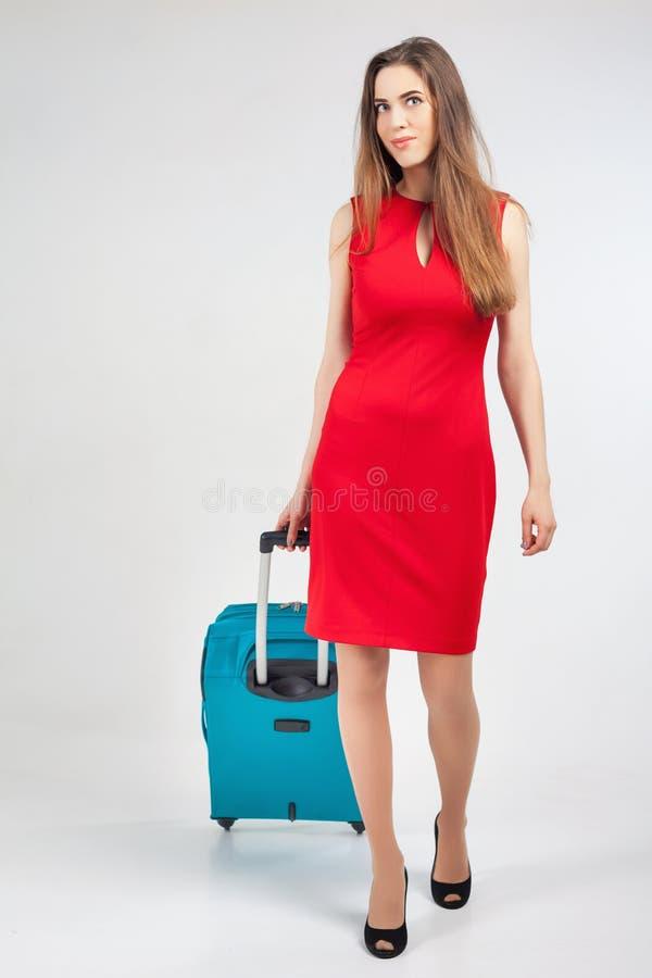 A mulher leva sua bagagem no terminal de aeroporto imagem de stock