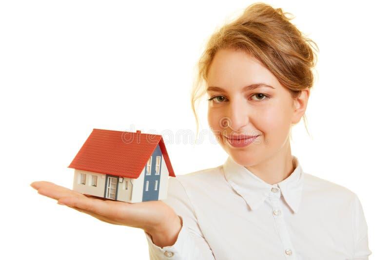 A mulher leva uma casa da família em sua mão foto de stock