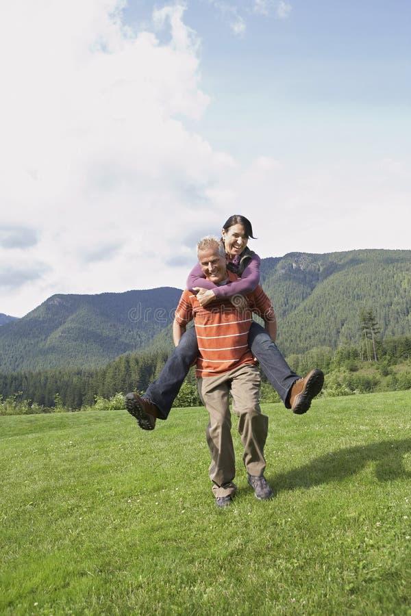 A mulher levando do homem ativo suporta sobre no prado fotografia de stock