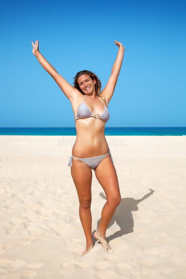 A mulher levantou suas mãos acima na praia imagem de stock