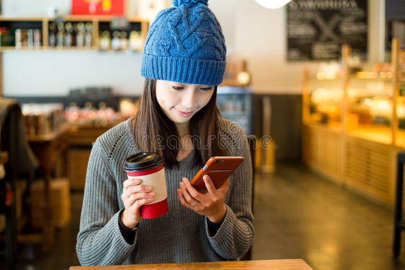 Mulher lida no telefone celular na cafetaria interna fotografia de stock