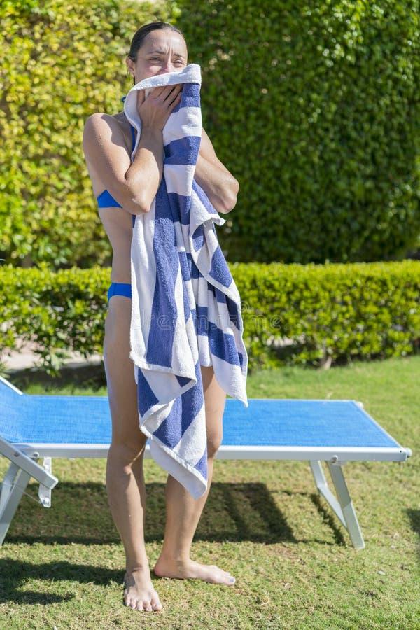 A mulher limpa fora uma toalha perto do sunbed foto de stock royalty free