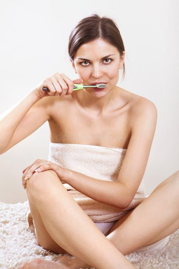 A mulher limpa seus dentes fotos de stock