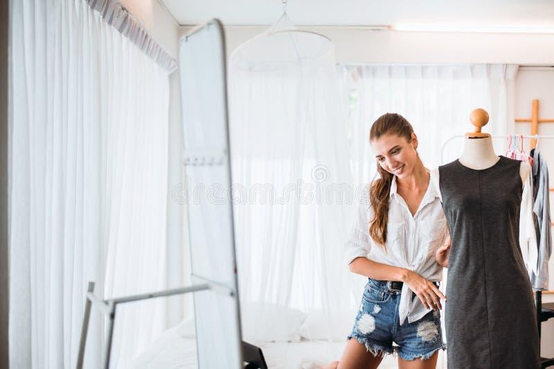 Mulher linda jovem de pé na loja de roupas e escolhendo vestidos, feliz e sorridente, conceito de moda e estilo de vida imagem de stock