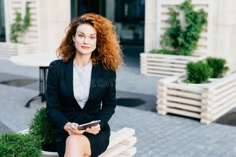 Mulher lindo bonita com cabelo espesso ondulado, terno formal vestindo, pés cruzados de assento no café exterior, guardando o tab imagens de stock