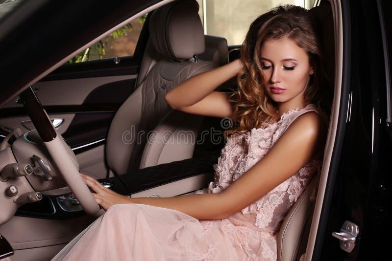 A mulher lindo com cabelo escuro veste o vestido luxuoso, levantando no carro preto foto de stock royalty free