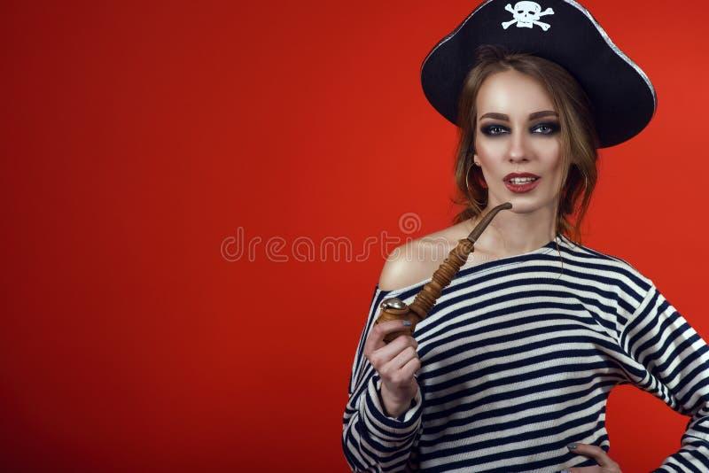 Mulher lindo com o traje vestindo do pirata da composição provocante e o chapéu armado que guardam uma tubulação de cigarro cinze foto de stock royalty free
