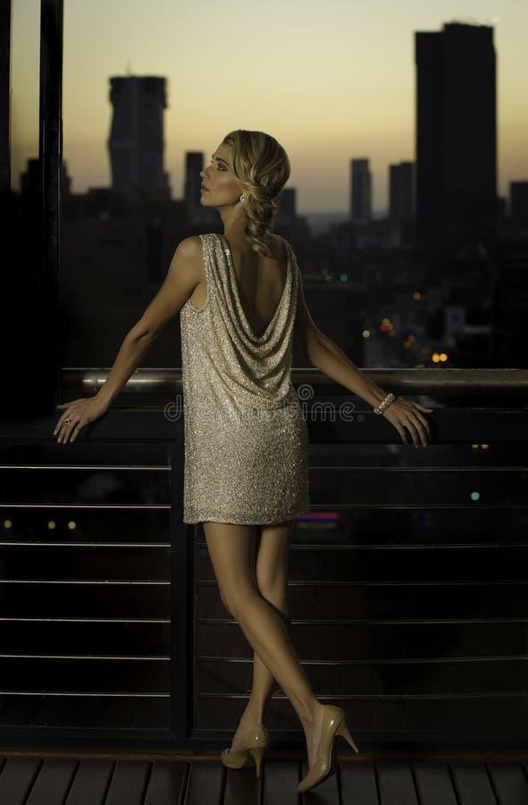 Mulher lindo no desgaste do cocktail que levanta com o por do sol sobre a cidade no fundo foto de stock royalty free