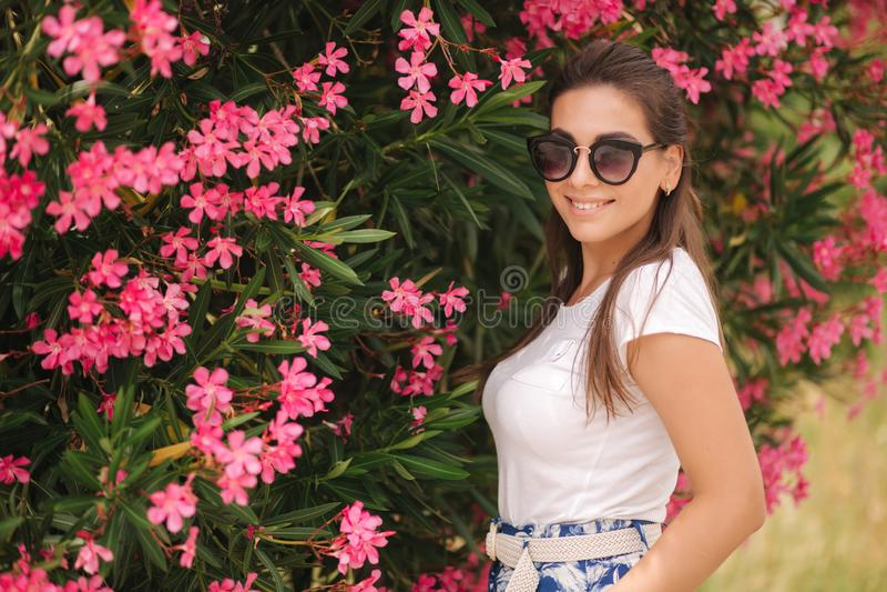 A mulher lindo nos óculos de sol está em flores bonitas Retrato da jovem mulher sorrida feliz imagens de stock