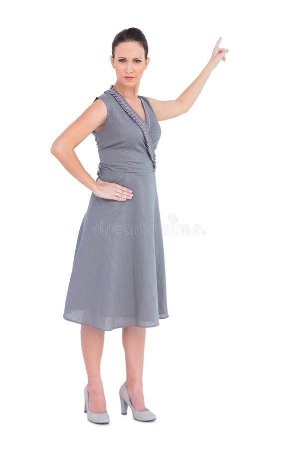 Mulher lindo olhando de sobrancelhas franzidas no vestido elegante que indica o sentido imagem de stock royalty free