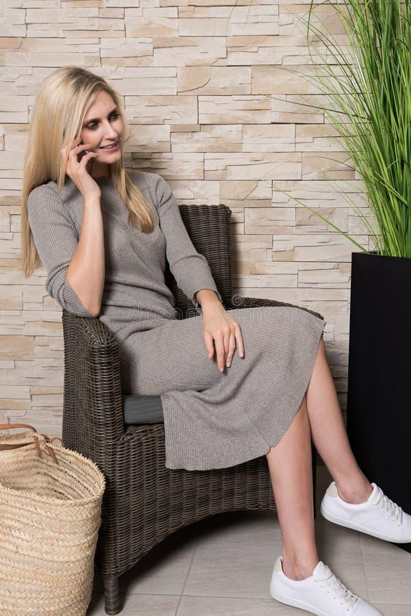 Mulher lindo que fala no telefone celular em uma área de espera imagens de stock royalty free