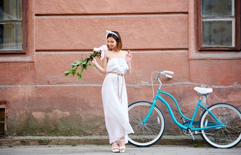 Mulher lindo que guarda as flores que levantam perto de sua bicicleta imagens de stock royalty free