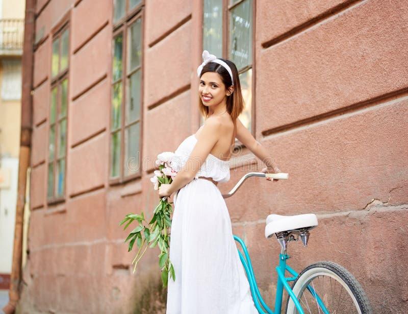 Mulher lindo que guarda as flores que levantam perto de sua bicicleta fotografia de stock royalty free