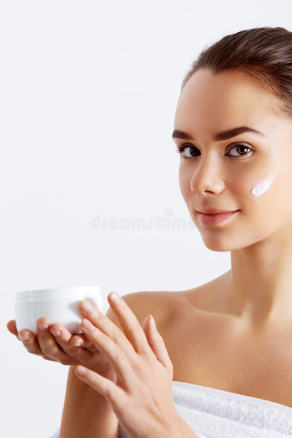 Mulher lindo que guarda o creme de pele Este é o melhor produto cosmético Guardando a loção hidratando Conceito da beleza fotos de stock