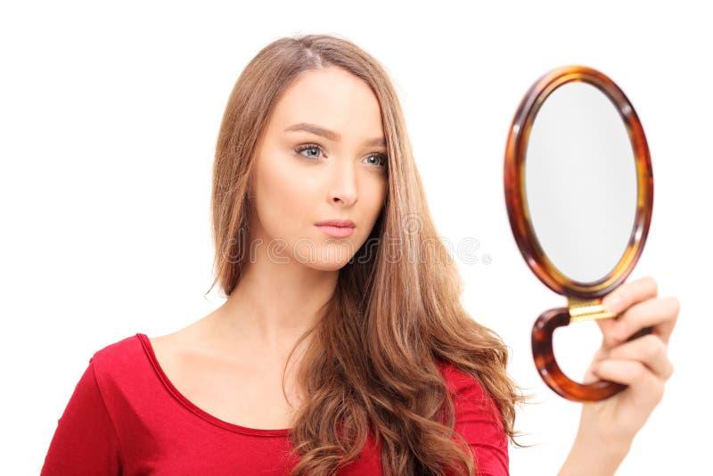 Mulher lindo que olha-se em um espelho fotografia de stock
