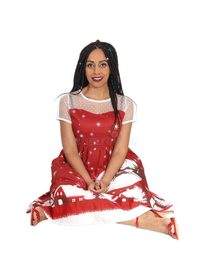 Mulher lindo que senta-se no assoalho em um vestido vermelho imagens de stock
