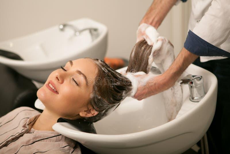 Mulher lindo que tem seu cabelo lavado pelo cabeleireiro foto de stock