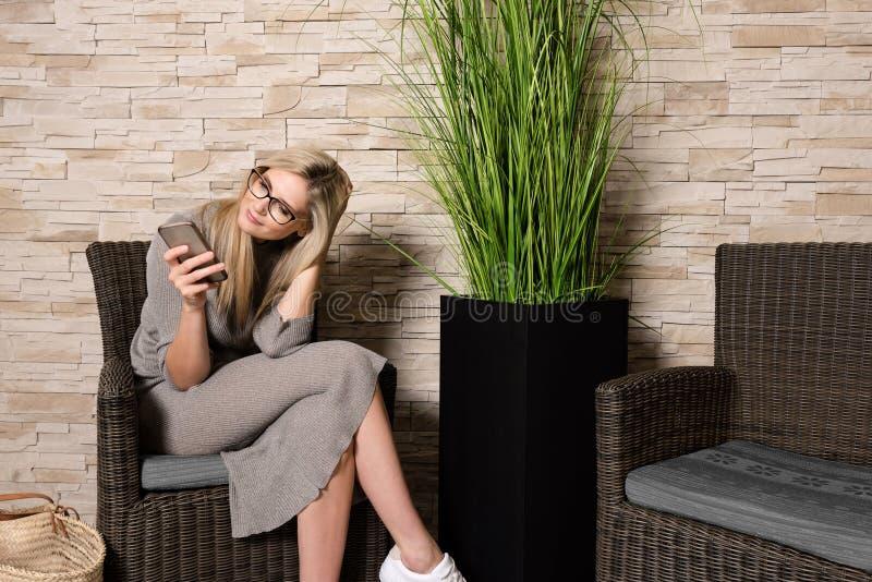 Mulher lindo que usa o telefone celular em uma área de espera foto de stock