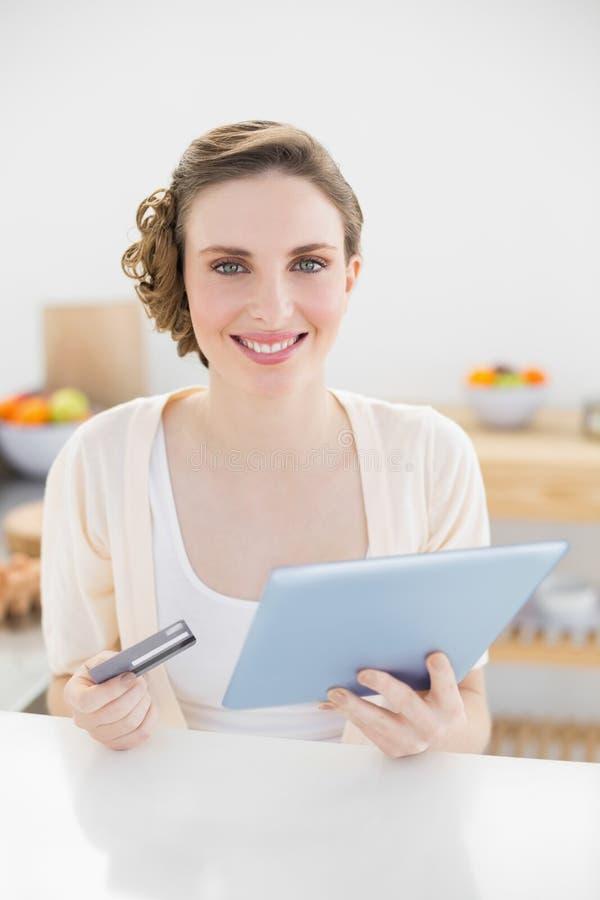 Mulher lindo que usa sua tabuleta para as compras ao domicílio que sentam-se em sua cozinha imagem de stock