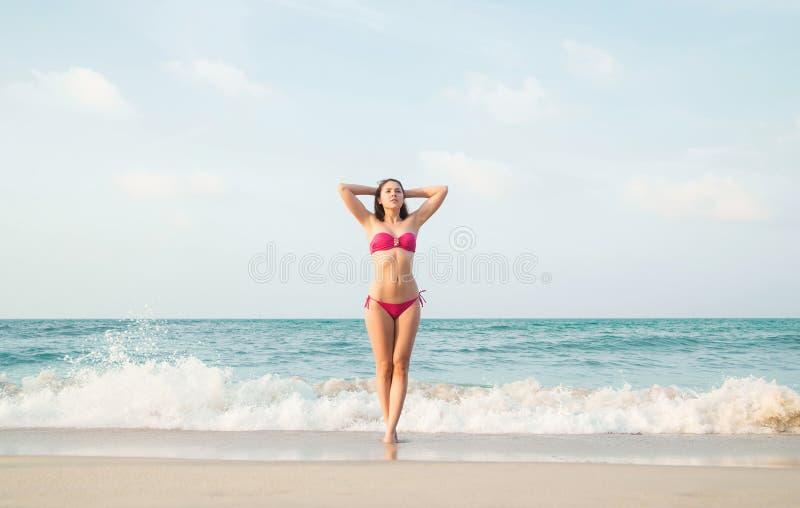 Mulher lindo, 'sexy', relaxado com o corpo do ajuste que tem as mãos atrás da cabeça na praia do verão fotos de stock royalty free
