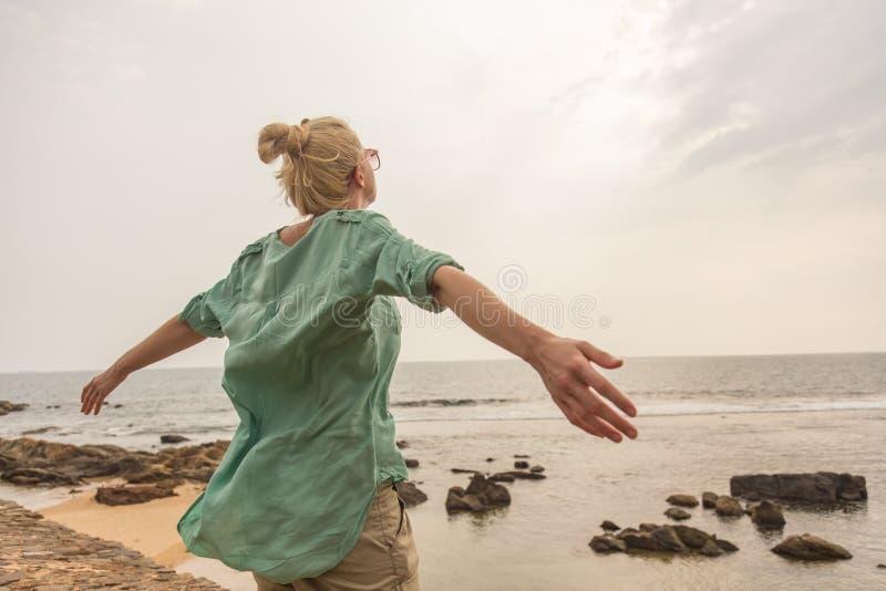 Mulher livre que aprecia o tempo ventoso na praia no dia nublado fotos de stock