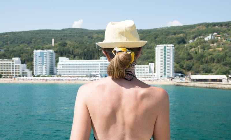 Mulher loira numa palha que olha para a praia arenosa em resort búlgaro imagem de stock royalty free