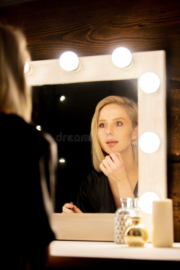 Mulher loira vestida perto do espelho de maquiagem fotografia de stock royalty free