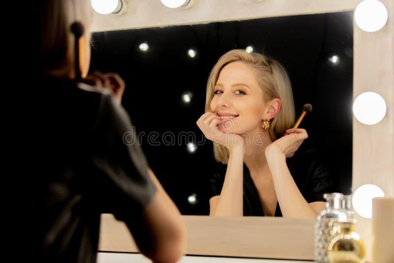 Mulher loira vestida perto do espelho de maquiagem fotos de stock