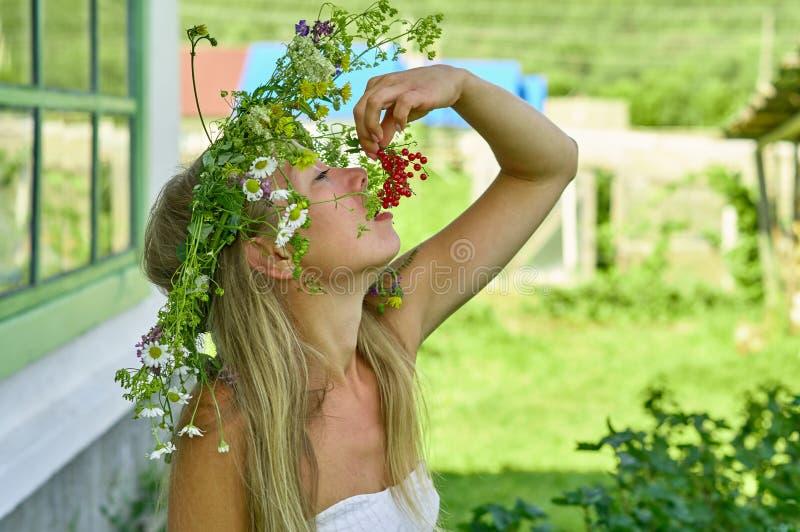 Mulher longo-branca bonita do cabelo para comer o corinto vermelho na jarda de sua casa de campo Dia de verão, quente e ensolarad imagens de stock royalty free