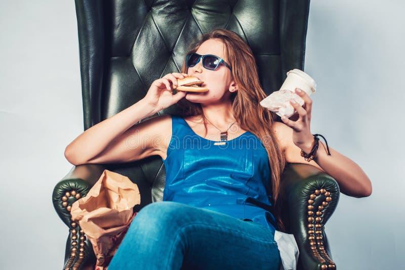 Mulher louca engraçada que come a comida lixo do Hamburger e fotos de stock royalty free
