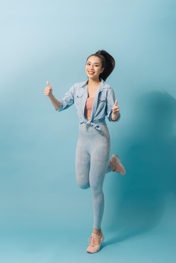 Mulher louca entusiasmado de encantamento que salta acima em claro - fundo azul foto de stock royalty free