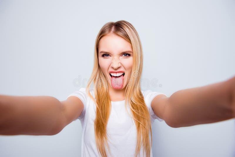 A mulher louca funky com cabelo louro está mostrando seus língua e tak fotografia de stock