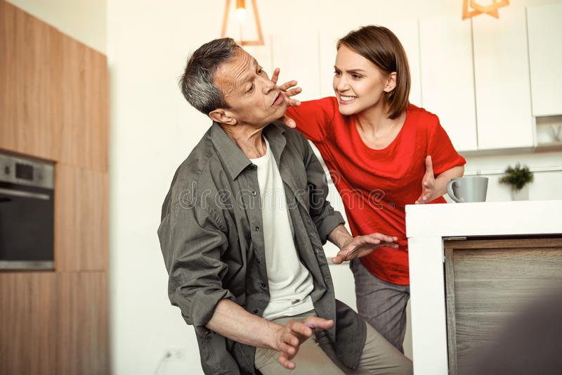 Mulher louca louca que golpeia a cara de seu marido chocado foto de stock