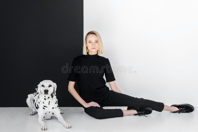 mulher loura à moda atrativa na roupa preta que senta-se perto da parede preto e branco imagens de stock