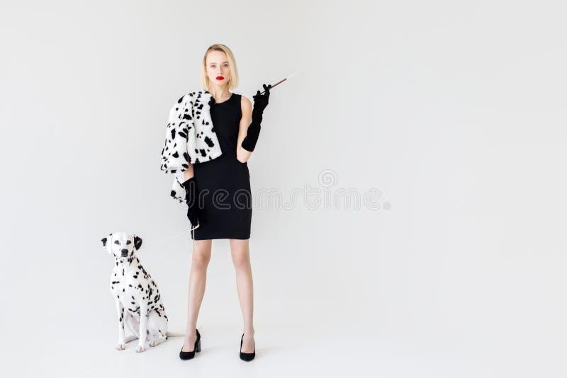 mulher loura à moda atrativa no vestido preto com cão dalmatian imagem de stock royalty free
