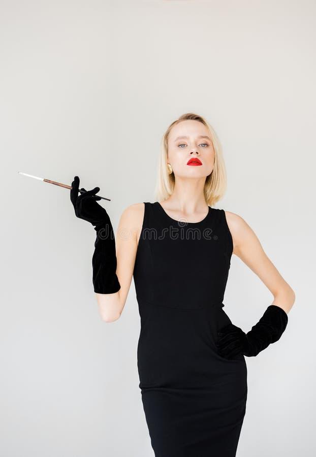 mulher loura à moda atrativa no vestido preto com cigarro imagens de stock
