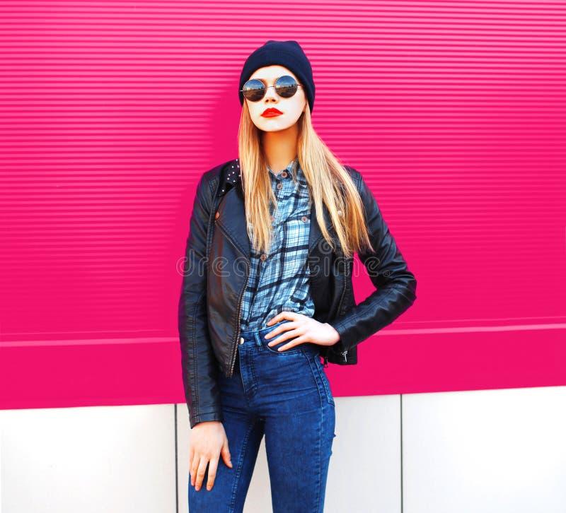 Mulher loura à moda do retrato da forma no revestimento do estilo do preto da rocha, chapéu que levanta na rua da cidade sobre a  imagens de stock