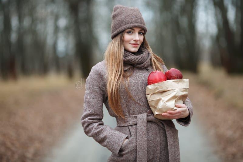 A mulher loura à moda em urbano na moda outwear o levantamento da aleia de Forest Park do tempo frio com pacote de maçãs vermelha fotografia de stock