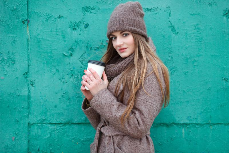 A mulher loura à moda em urbano na moda outwear o levantamento do tempo frio contra o fundo pintado verde do metal do grunge imagens de stock royalty free