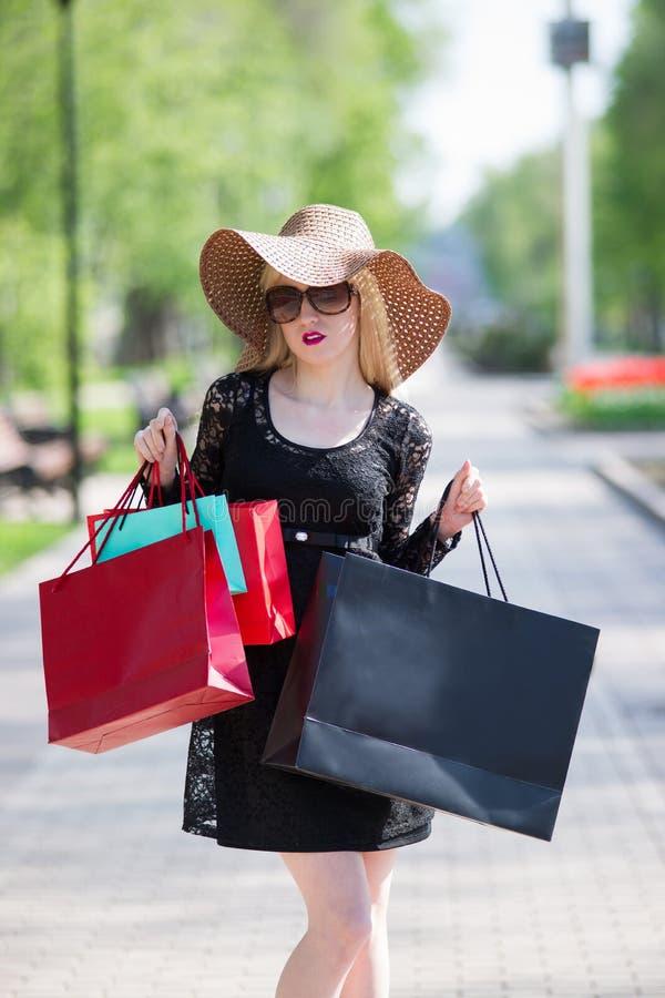 Mulher loura à moda no vestido, em óculos de sol e no chapéu pretos com sacos de compras andando na cidade foto de stock