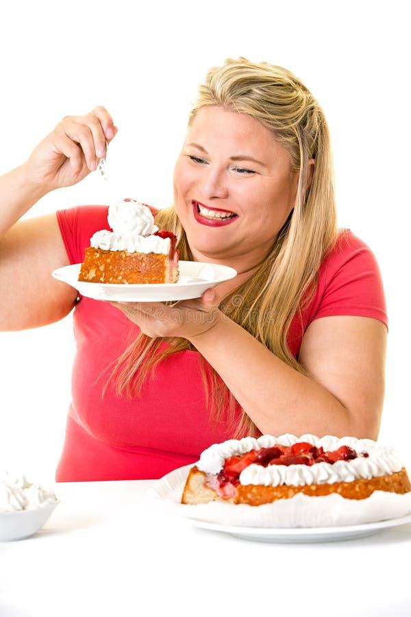 Mulher loura ávida com os bolos de creme da engorda fotografia de stock royalty free