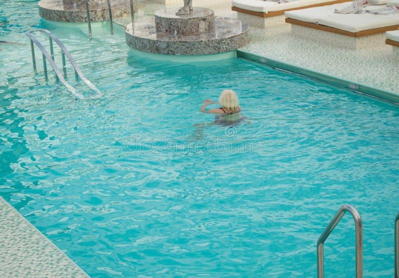 A mulher loura adulta aprecia nadar em uma associação luxuoso em um navio de cruzeiros imagem de stock royalty free
