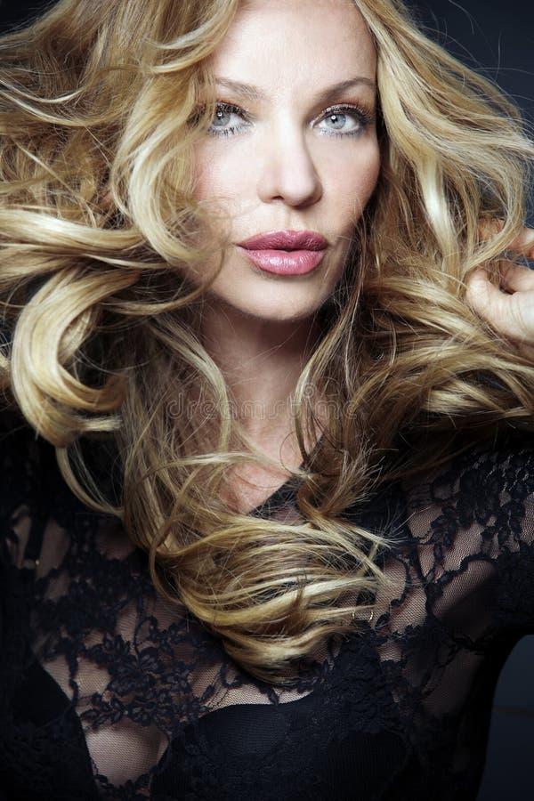 Mulher loura atrativa com cabelo curly longo. imagens de stock