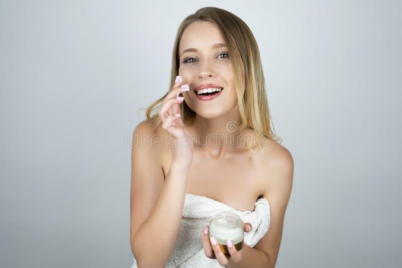 Mulher loura atrativa de sorriso que aplica o creme da beleza em seu fundo branco isolado cara fotografia de stock