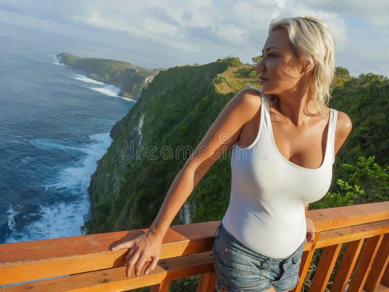 Mulher loura atrativa e feliz do turista que olha a vista impressionante da praia bonita do penhasco do mar na apreciação do pont fotografia de stock royalty free